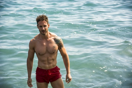 Young muscle man standing in sea water, shirtless with swimming suit