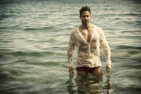 Attractive bodybuilder in the sea with wet shirt on, serious expression