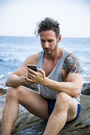 athletic type: Athletic man at the seaside using cell phone to type message while looking at the sea. Stock Photo