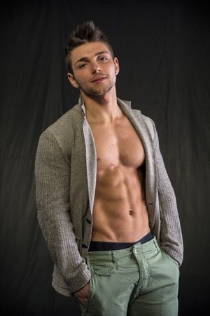 man profile: Confident, attractive young man with open jacket on muscular torso, ripped abs and pecs. Side view Stock Photo