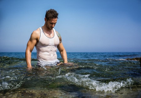 Attractive bodybuilder in the sea with wet t-shirt on, serious expression