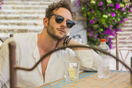 goodlooking: Portrait of stylish good-looking man in sunglasses holding bottle of water at table in cafe Stock Photo