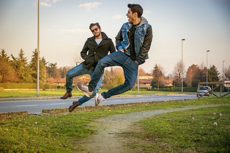 in unison: Pair of Young Men Leaping into Air and Clicking Heels Together in Unison While Walking on Path in Urban Park Alongside Paved Road at Sunset Stock Photo