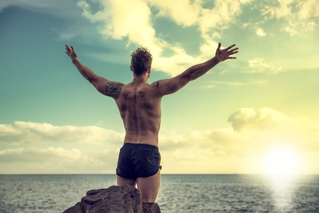 beach hunk: Muscular young man on the beach seen from the back, with arms open enjoying the sensation of freedom