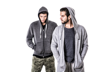 sport clothes: Two young men wearing military and sport clothes. Wearing hoods on heads. Studio shot.