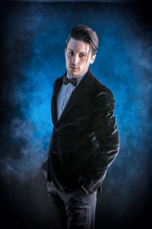 confidently: Young businessman confidently posing and looking at camera, wearing suit, on dark background Stock Photo