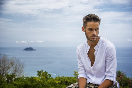 italian sea: Handsome Young Man in Trendy Attire, n a Sunny Summer Day with Italian Sea Coast in the Distance, Wearing a White Shirt