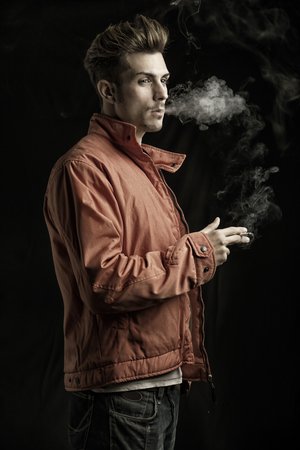 dean: Handsome young man smoking cigarette, dressed as James Dean with red jacket on dark background