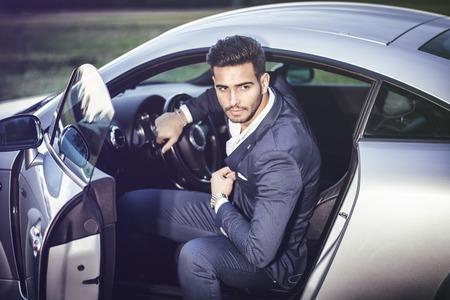 Portrait der jungen attractiave Mann im Business-Anzug sitzt in seinem neuen stilvollen Auto im Freien auf dem Land