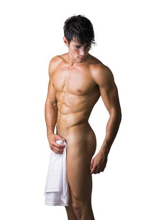 Retrato de hombre joven y guapo desnudo con lánguida mirada que cubre la entrepierna con una toalla o una camiseta, aislado en fondo blanco Foto de archivo