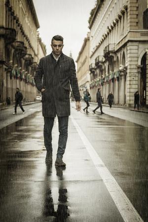 Volledige lengte van de jonge man in de jas lopen onder regen langs de straat in de stad met sigaretten. Stockfoto
