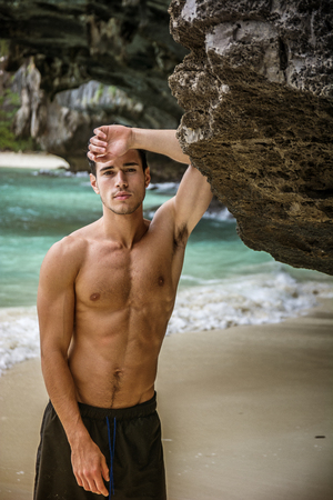 Half body shot of a handsome young man standing on a beach in Phuket Island, Thailand, shirtless wearing boxer shorts, showing muscular fit body, looking at camera Фото со стока