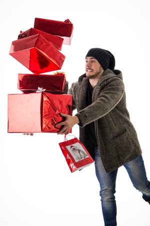 Portrait of bearded man in hat dropping pile of presents. Studio shot