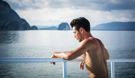 Portrait of young handsome bare chested brunet man?looking away against seascape on a boat or ship, leaning on handrail