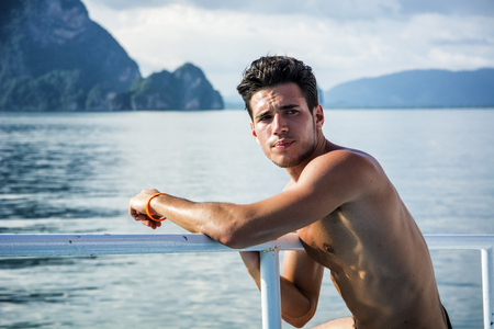 Portrait of young handsome bare-chested brunet man?looking away against seascape on a boat or ship, leaning on handrail. Stock Photo