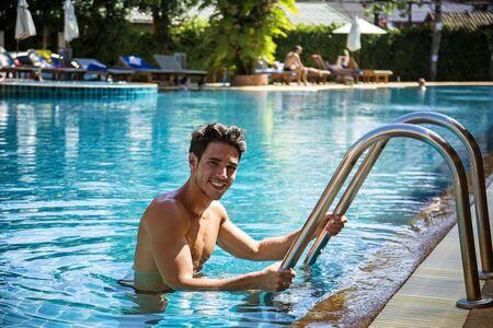 and the horizontal man: Smiling man walking out of swimming pool and looking at camera. Horizontal outdoors shot
