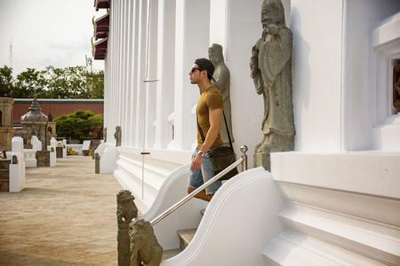 down the stairs: Vista lateral de un joven caminando por las escaleras del templo budista en Bangkok, Tailandia y mirando directamente. Foto de archivo