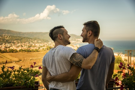 Back view of homosexual couple embracing nd looking at each other on background of resort. Standard-Bild