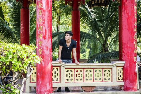 and the horizontal man: Young handsome man standing in Chinese temple in Bangkok, Thailand. Horizontal outdoors shot