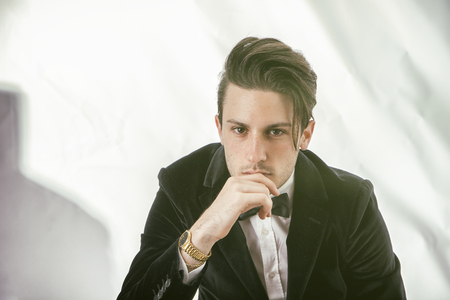 confidently: Young businessman confidently posing and looking at camera, wearing suit, on white background