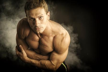Handsome shirtless bodybuilder shot from above, standing on dark smoky background Stock Photo