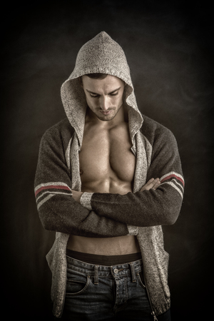 hooded vest: Confident, attractive young man with open vest on muscular torso, ripped abs and pecs. On dark background