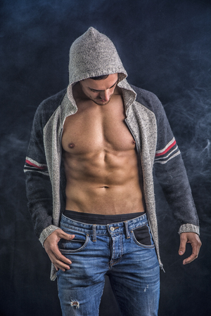 pecs: Confident, attractive young man with open vest on muscular torso, ripped abs and pecs. On dark background