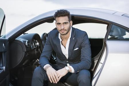 Portret van een jonge attractiave man in pak zitten in zijn nieuwe stijlvolle auto buiten in de natuur Stockfoto