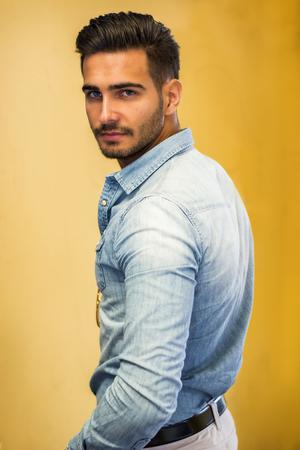 Attraktiver junger Mann, der gegen die bunte Wand, Kamera betrachtend sitzt Standard-Bild
