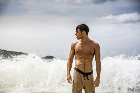 Half body shot of a handsome young man standing on a beach, shirtless wearing boxer shorts, showing muscular fit body, with big foamy wave surf behind him