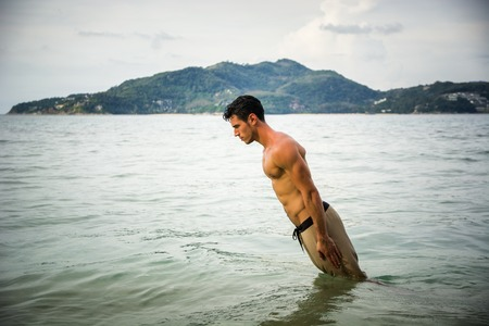 and the horizontal man: Straighten muscular man diving to the water on the background of green mountain. Horizontal outdoors shot.