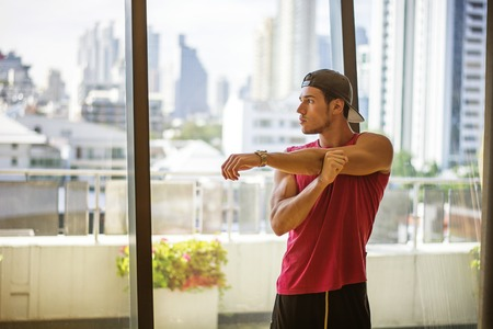 laying abs exercise: Attractive muscular young man in gym working out, doing exercises in front of wide windows overlooking modern city skyscrapers