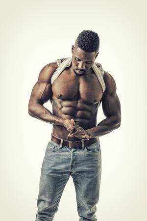 Uomo adatto di bella palestra nera che mostra il suo ABS sexy di addominali scolpiti mentre guardando giù. Su sfondo bianco Archivio Fotografico