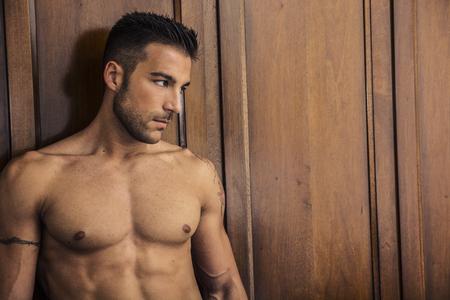#71052311   Sexy Gut Aussehender Junger Mann In Seinem Schlafzimmer Stand  Mit Nacktem Oberkörper Gelehnt Holzschrank. Mit Blick Auf Eine Seite