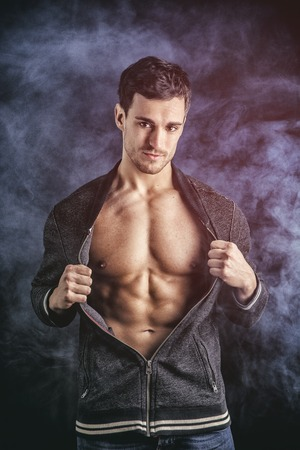hooded vest: Confident, attractive young man opening vest on muscular torso, ripped abs and pecs. On dark smoky background