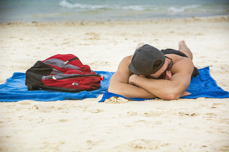 ruck sack: Portrait of a man in a cap and sunglasses sunbathing on the beach on towel, next to backpack Stock Photo