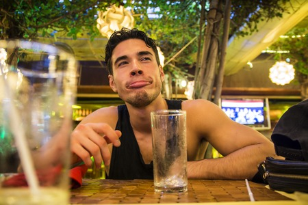 and the horizontal man: Cheerful man grimacing in the bar. Horizontal indoors shot.