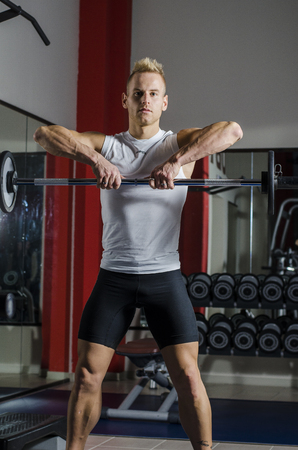 Handsome young man training shoulders lifting barbell, standing in a gym