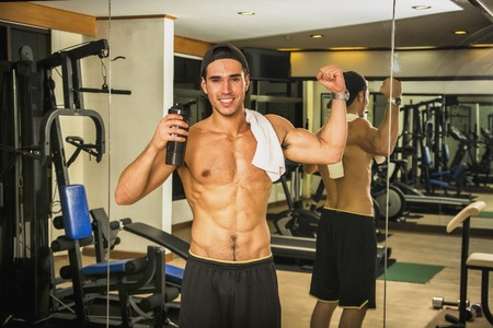 and the horizontal man: Horizontal indoors shot of young shirtless man with a bottle showing the muscles in a gym.