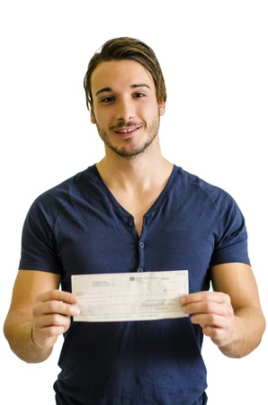Happy, smiling young man with check or cheque in hands, looking at camera photo