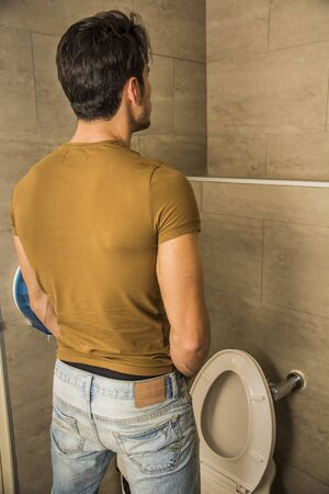 piddle: Rear View of a Young Man in Black Outfit Peeing at the Toilet Inside his Bathroom. Stock Photo
