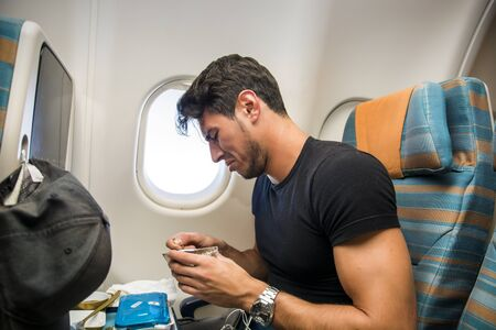 insipid: Young man feeling disgusted after tasting insipid food in the airplane. Horizontal indoors shot. Stock Photo