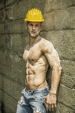 Handsome muscular construction worker standing shirtless in front of a concrete wall, looking at camera