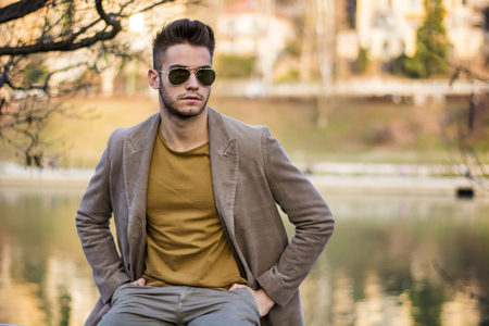 Handsome young man sitting in front of river in a city, looking confident and relaxed Stock Photo