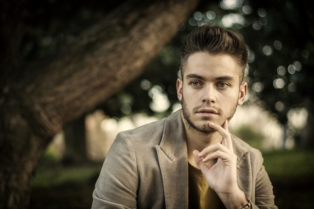 Handsome young man sitting in city park, looking confident and relaxed in autumn or spring evening