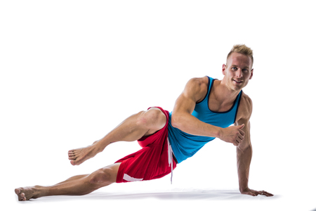 Blond athletic young man exercizing on the floor, isolated on white background in studio shot Stock Photo