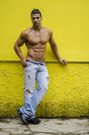 Handsome, muscular young man shirtless posing and standing against yellow wall Stock Photo