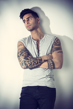 d2ec74eed Handsome tattooed young man wearing grey t-shirt, standing against light  background in studio