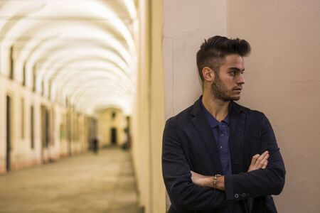 male fashion model: Handsome young man under cloisters in Italian city center, Turin, at night