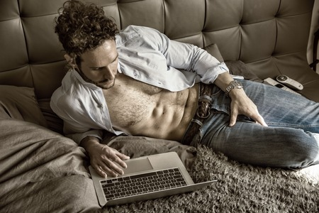 Sexy handsome man laying with open shirt on his bed with laptop computer working or surfing the internet